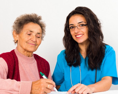 elder woman with nurse filling up forms